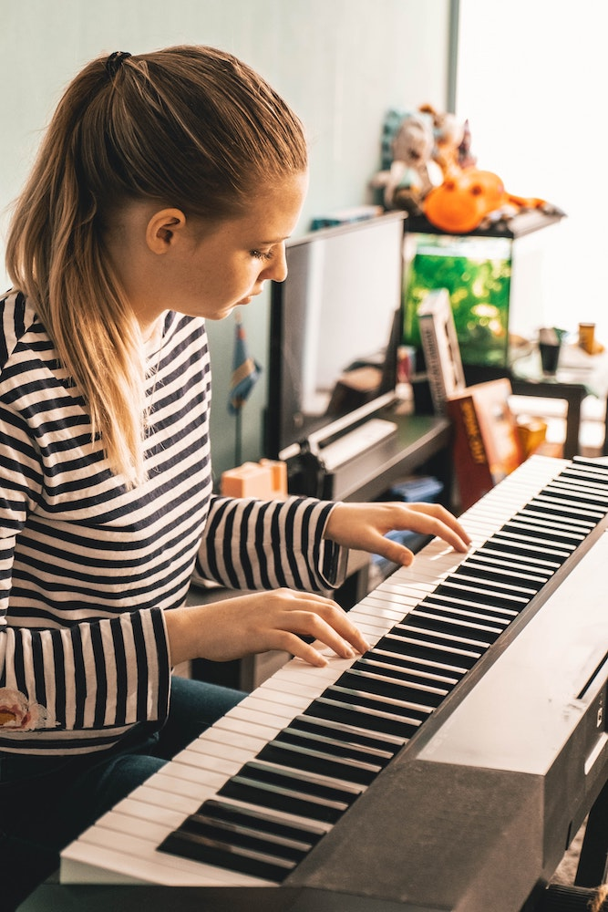 Girl plays piano watching her fingers