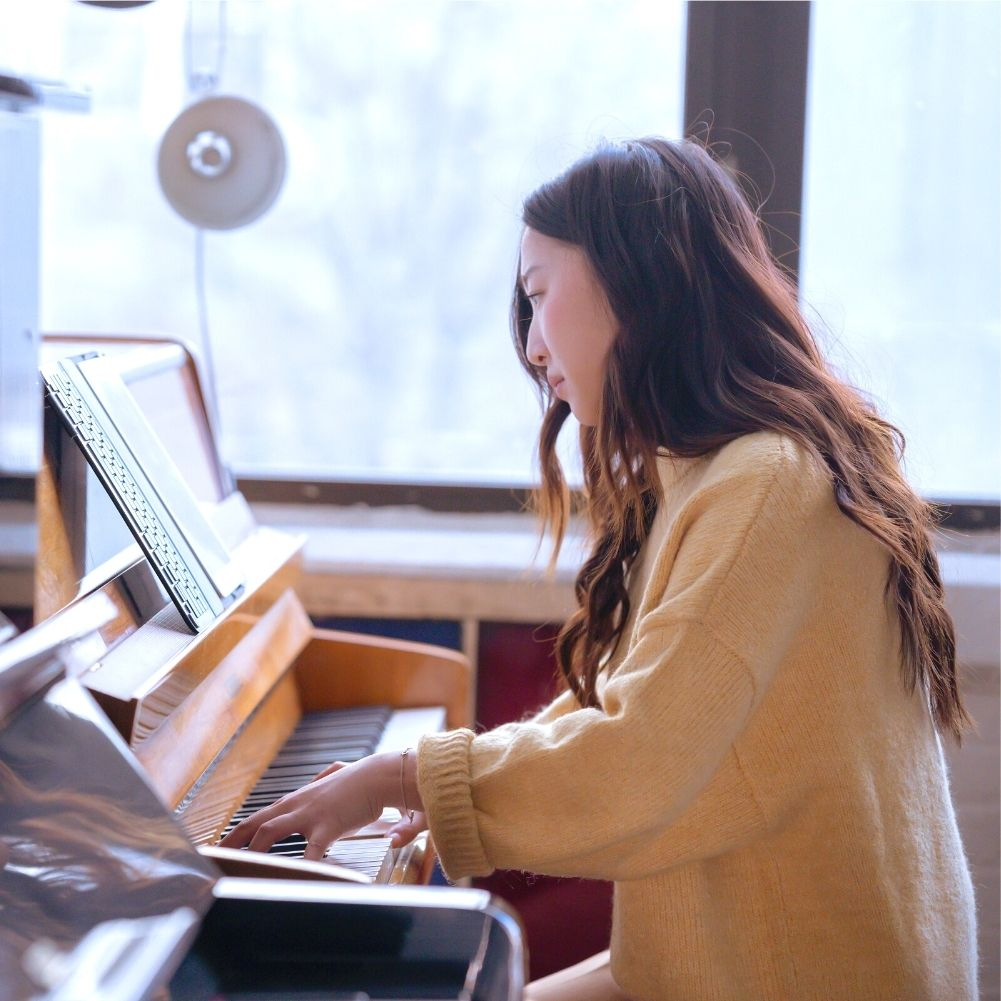 adult piano student in red shirt